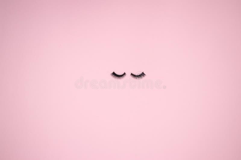 在桃红色背景的眼睛鞭子 库存照片