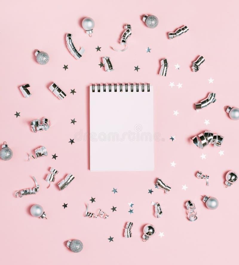 在桃红色背景的空的笔记本与银色圣诞装饰 明亮和欢乐 新年概念,顶视图,平的位置 免版税库存图片