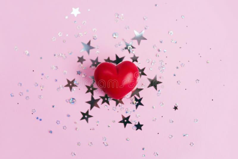 在桃红色背景的红心与星闪烁五彩纸屑 库存图片