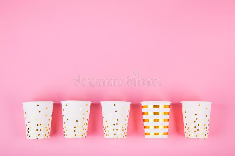 在桃红色背景的纸杯 免版税库存照片