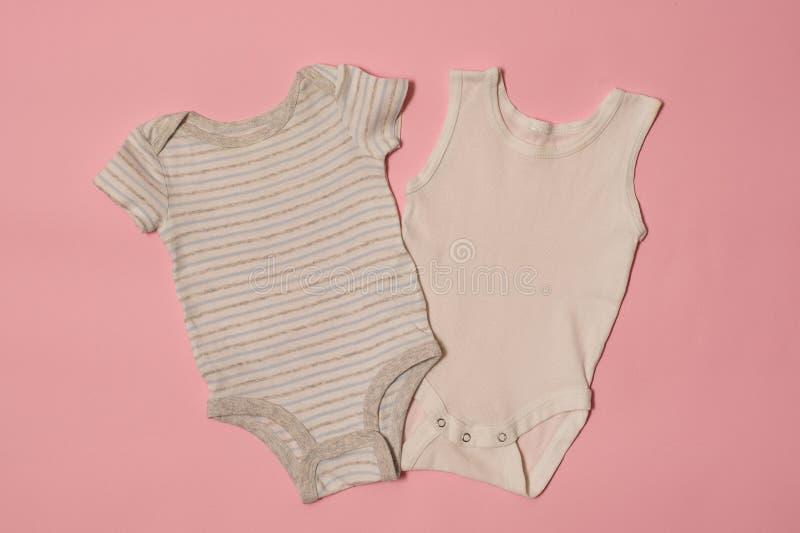 在桃红色背景的蓝色和白色婴孩紧身衣裤 秀丽蓝色聪慧的概念表面方式构成妇女 库存图片
