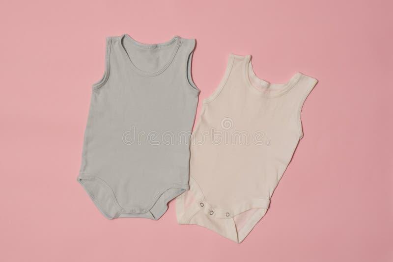 在桃红色背景的蓝色和白色婴孩紧身衣裤 秀丽蓝色聪慧的概念表面方式构成妇女 库存照片