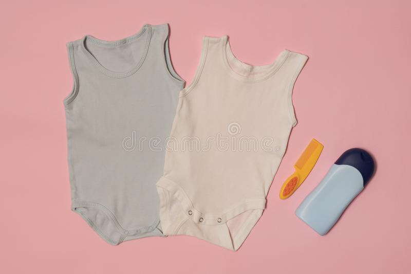 在桃红色背景的蓝色和白色婴孩紧身衣裤 赞誉 秀丽蓝色聪慧的概念表面方式构成妇女 免版税库存照片