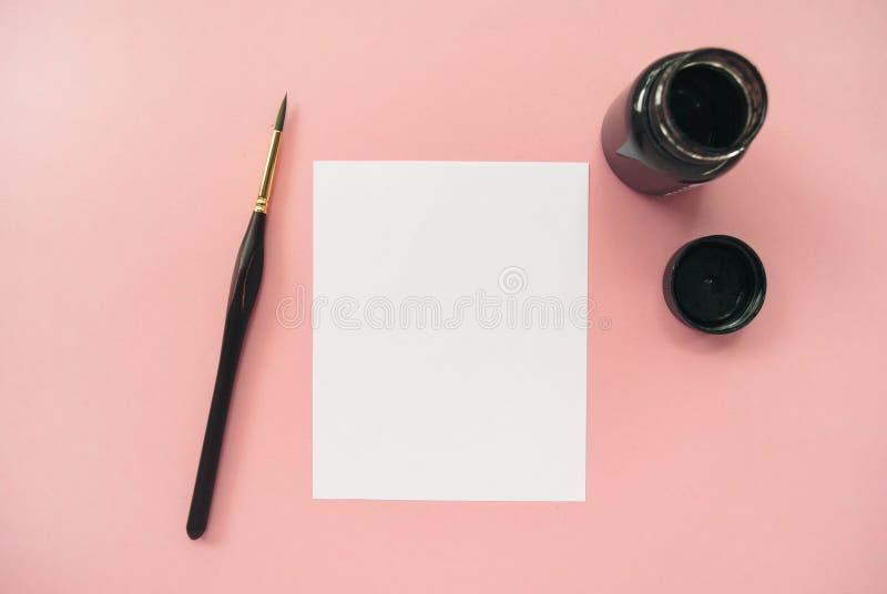在桃红色背景的被称呼的艺术家工作区 白皮书嘲笑与文本的空间 免版税库存照片