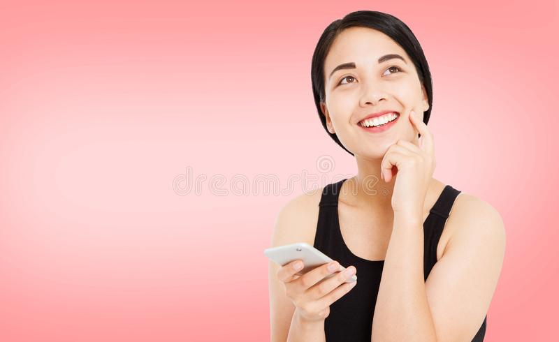 在桃红色背景的逗人喜爱的愉快的亚洲女孩举行电话 库存图片
