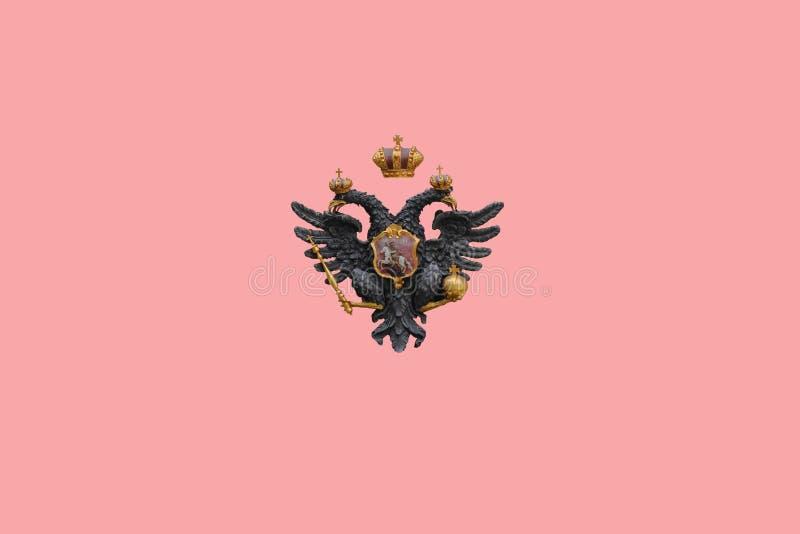 在桃红色背景隔绝的两头老鹰标志 库存照片