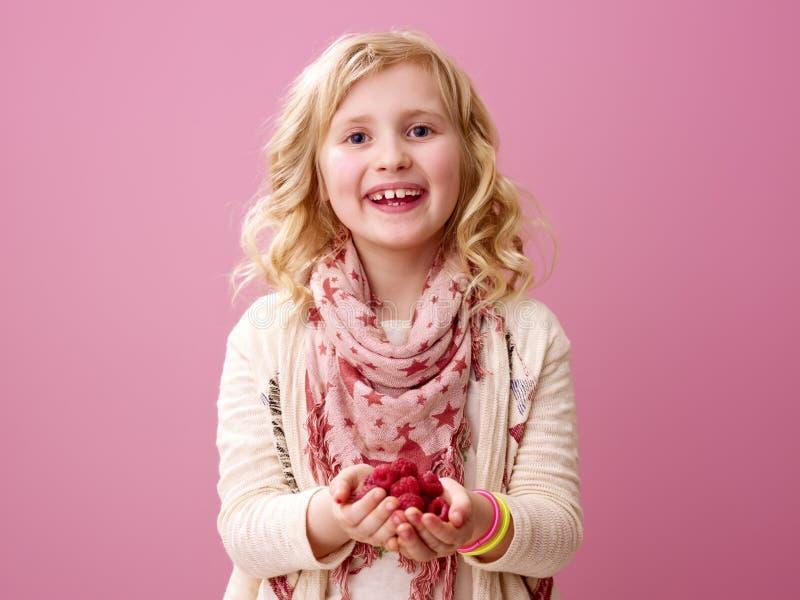 在桃红色背景隔绝的微笑的女孩显示莓 库存照片