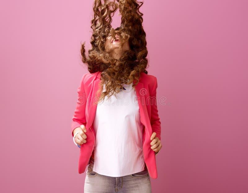 在桃红色背景隔绝的微笑的现代妇女震动头发 库存照片