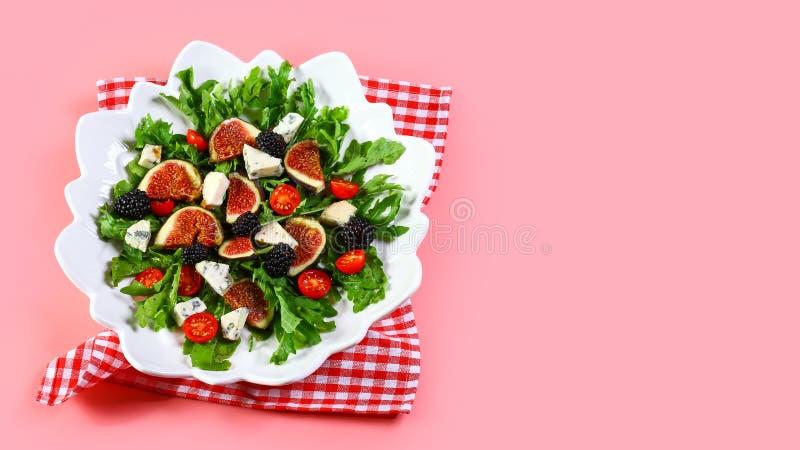 在桃红色背景隔绝的无花果、芝麻菜和乳酪沙拉 顶视图拷贝空间 免版税库存图片