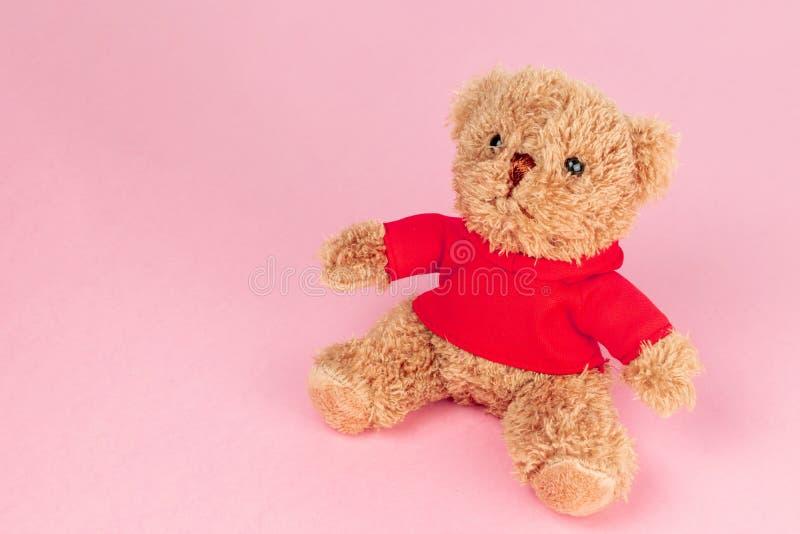 在桃红色背景隔绝的红色衬衣的玩具熊,假装为卡片庆祝 免版税图库摄影