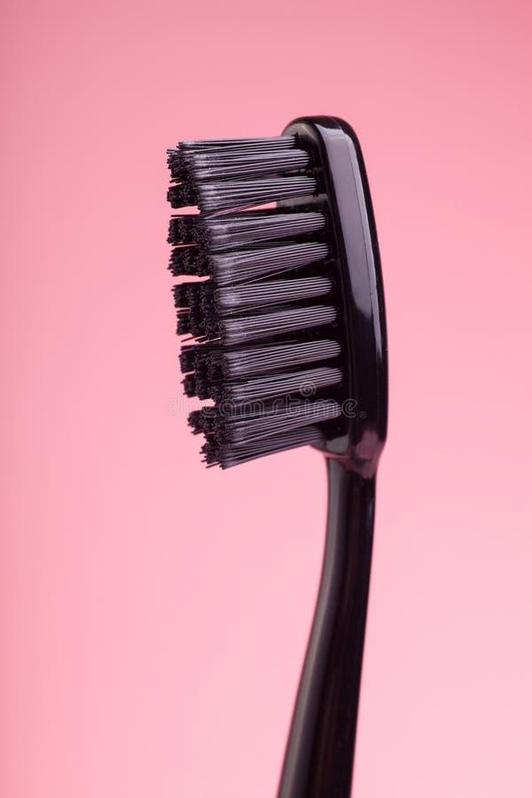在桃红色背景隔绝的新的黑牙刷 免版税库存图片
