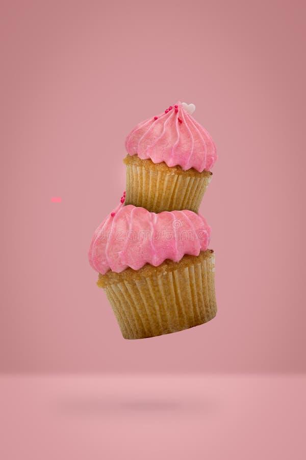 在桃红色背景,新的想法最小的概念的飞行的杯形蛋糕 免版税库存图片