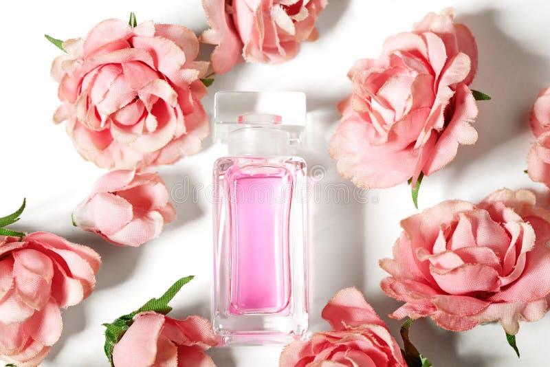 在桃红色花玫瑰的香水瓶 与豪华芳香parfume的春天背景 秀丽化妆用品射击 库存照片