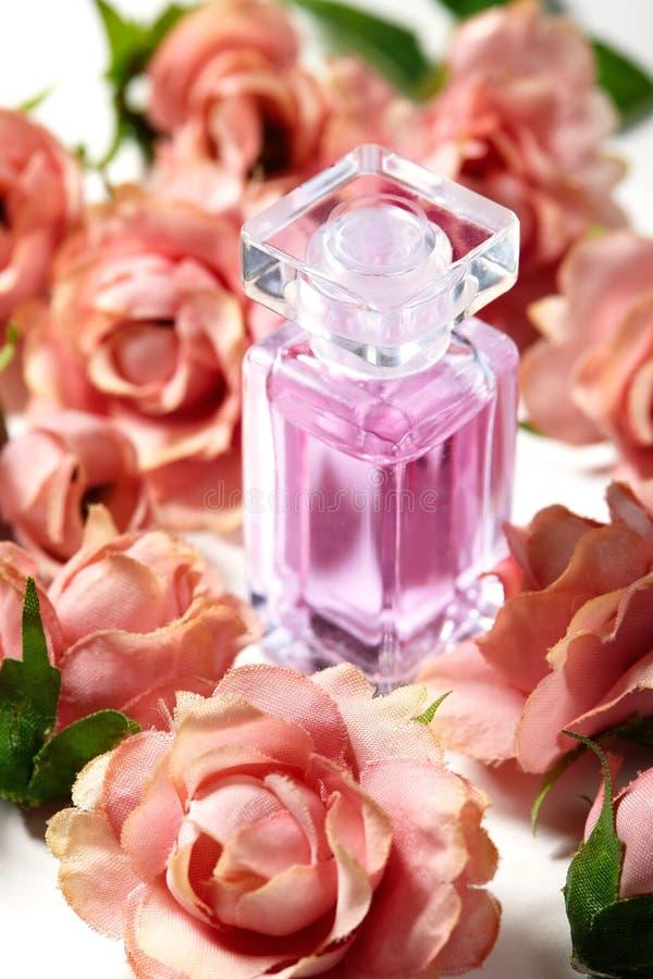 在桃红色花玫瑰的香水瓶 与豪华芳香parfume的春天背景 秀丽化妆用品射击 免版税图库摄影