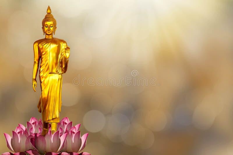 在桃红色莲花的金黄菩萨雕象在被弄脏的金黄bokeh后面 免版税库存图片