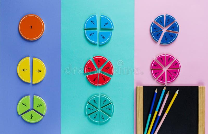 在桃红色蓝色紫罗兰明亮的背景的五颜六色的算术分数 孩子的有趣的算术 教育,回到学校概念 免版税库存图片
