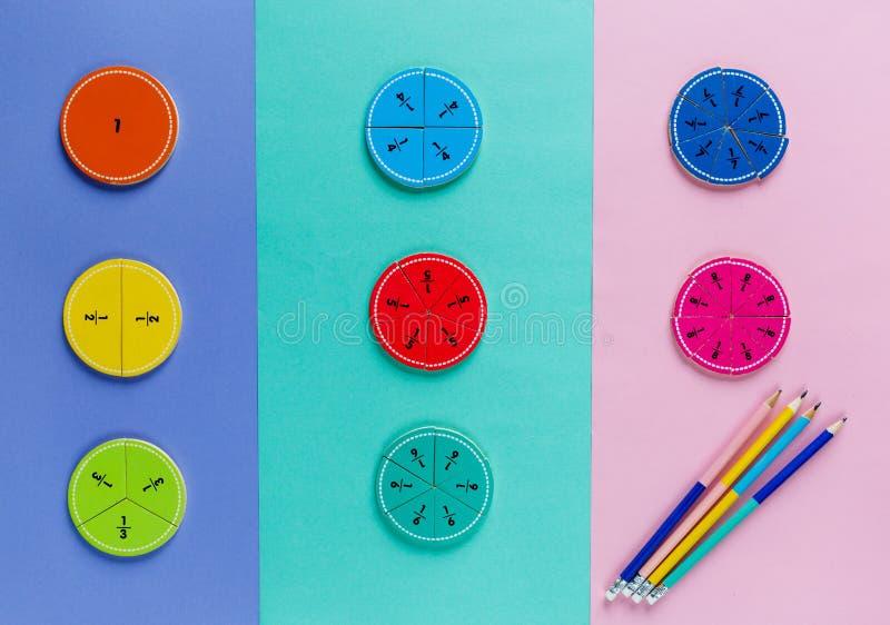 在桃红色蓝色紫罗兰明亮的背景的五颜六色的算术分数 孩子的有趣的算术 教育,回到学校概念 免版税图库摄影