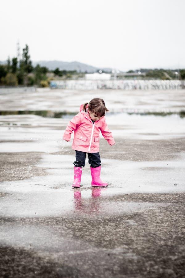 在桃红色衣裳打扮的孩子跳跃在水坑 库存图片