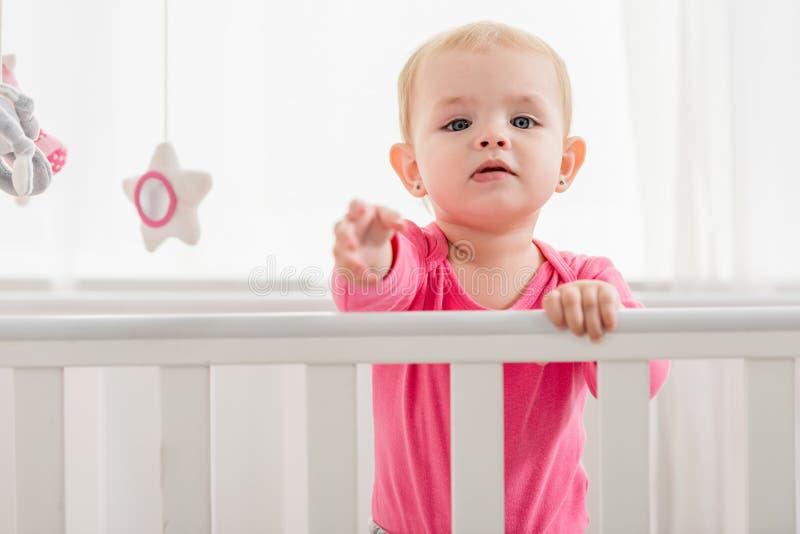 在桃红色衬衣身分的可爱的孩子在小儿床和到达手 库存图片