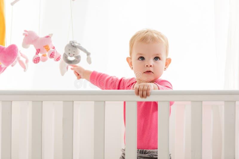 在桃红色衬衣身分的可爱的孩子在小儿床和接触玩具和 免版税库存图片