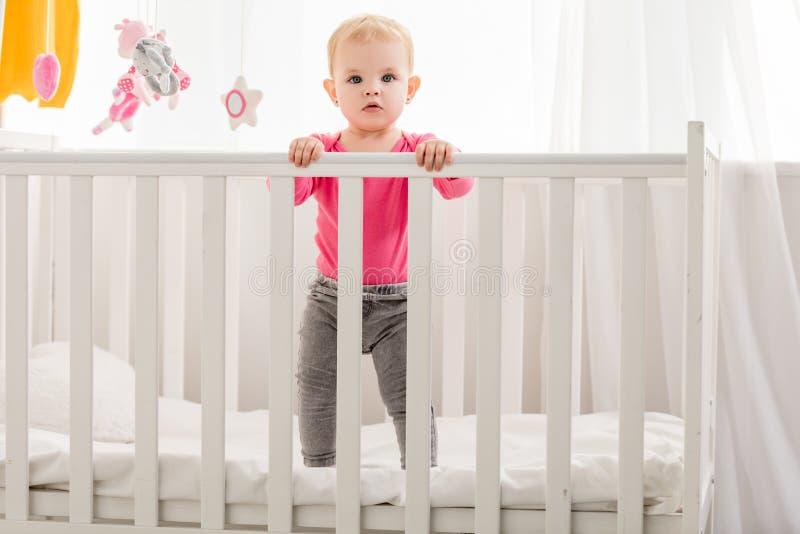 在桃红色衬衣身分的可爱的孩子在小儿床和看 免版税库存图片