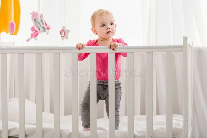 在桃红色衬衣身分的可爱的孩子在小儿床和 免版税库存图片
