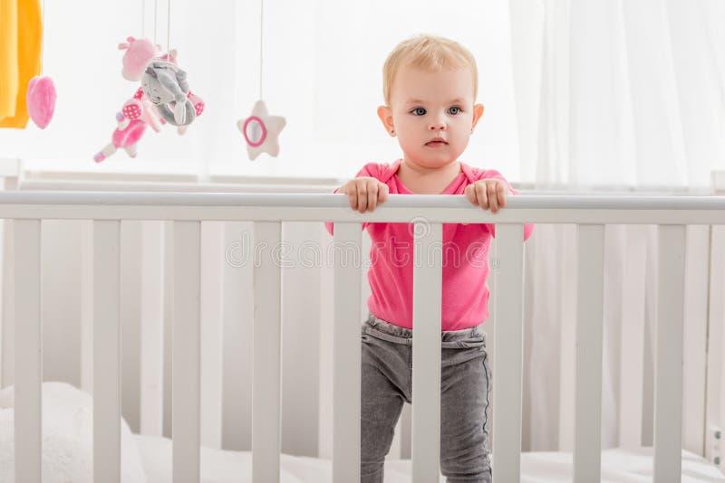 在桃红色衬衣身分的可爱的孩子在小儿床和 库存图片