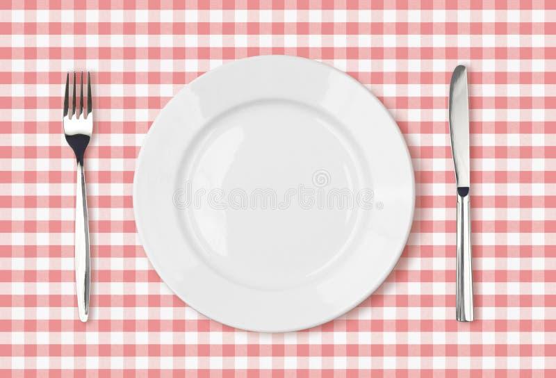 在桃红色野餐桌布的空的菜盘顶视图 免版税图库摄影