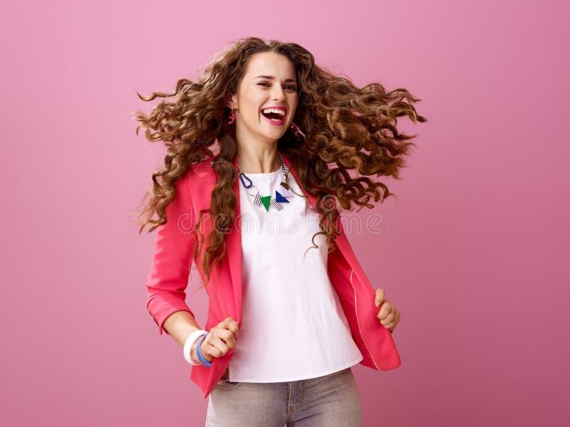 在桃红色震动的头发隔绝的微笑的时髦妇女 库存照片