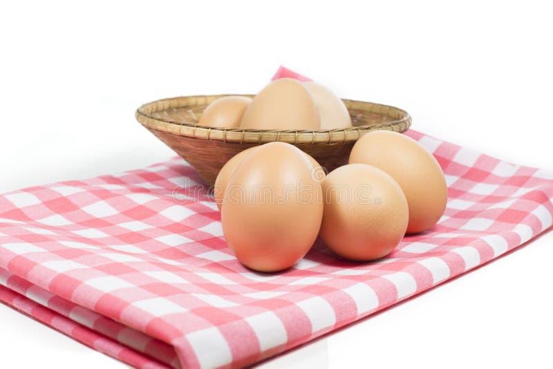 在桃红色颜色格子花呢披肩的在白色背景的鸡蛋和篮子 图库摄影