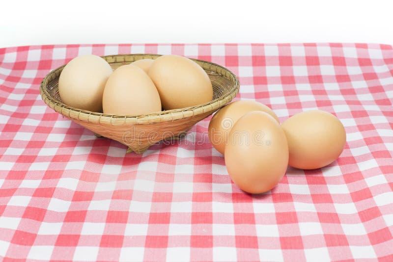 在桃红色颜色格子花呢披肩的在白色背景的鸡蛋和篮子 免版税库存照片