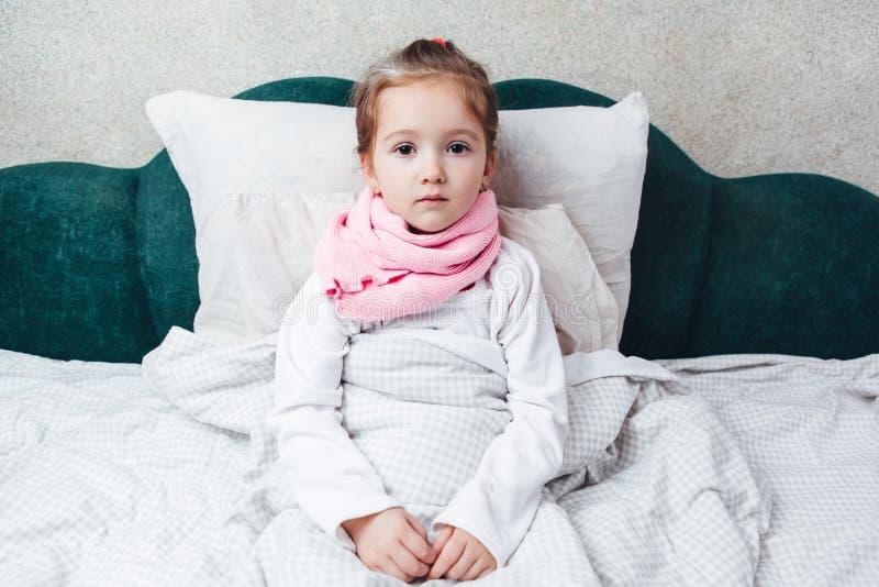 在桃红色围巾的床上的病的小女孩 库存照片