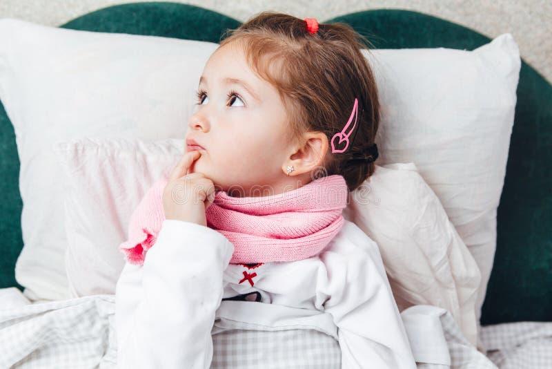 在桃红色围巾的床上的病的小孩 免版税图库摄影