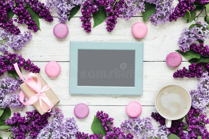 在框架的空白的照片卡片由与咖啡杯、礼物盒和蛋白杏仁饼干的淡紫色花制成在白色木桌 库存图片