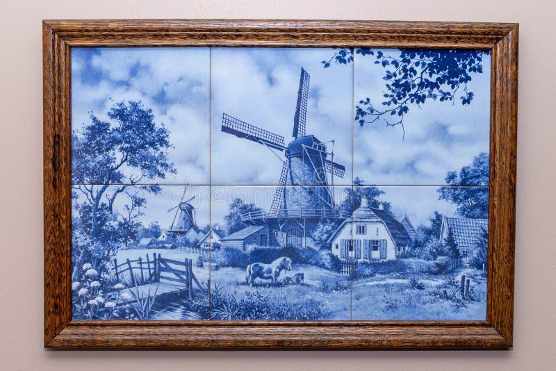 在框架,从荷兰/荷兰的一份纪念品的六个德尔福特蓝色瓦片 垂悬在做风车和典型的农厂场面的墙壁上 免版税库存照片