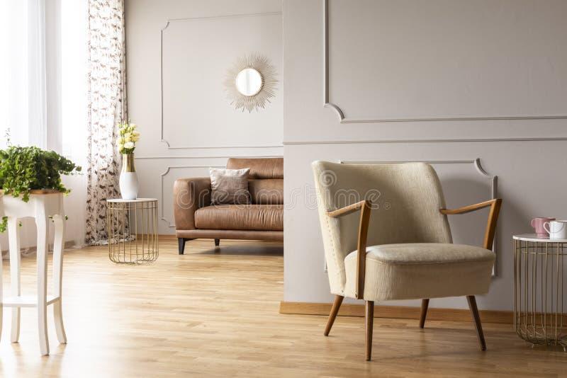 在桌、葡萄酒扶手椅子、花瓶有花的和舒适的皮革长沙发上的绿色植物有枕头的在宽敞客厅 免版税库存图片