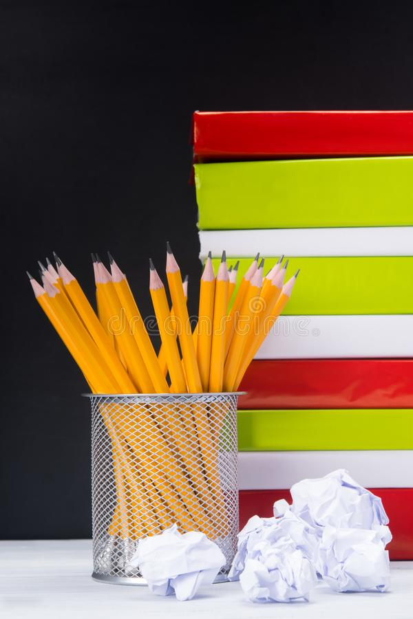 在桌上与铅笔的一个杯座,在与书的黑背景 免版税库存图片