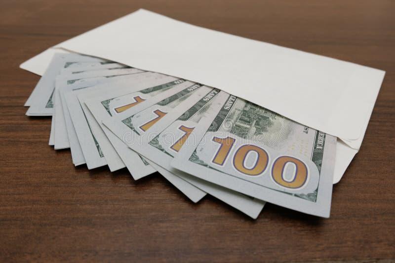 在桌上是有许多一百元钞票的一个白色信封 概念腐败,违反法律,财政 免版税库存照片