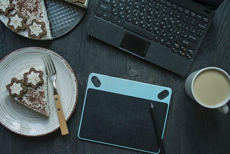 在桌上是膝上型计算机、图形输入板、蛋糕和一杯咖啡 r 工作环境 o ?? 库存图片