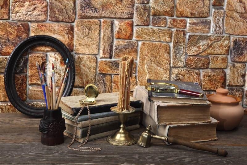 在桌上是:旧书、一个蜡蜡烛在一个古铜色烛台,一个陶瓷罐、一只怀表、缨子在一块被雕刻的玻璃和a 免版税库存图片