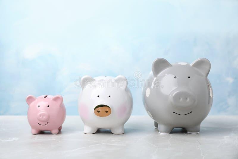 在桌上的三逗人喜爱的存钱罐 免版税库存照片
