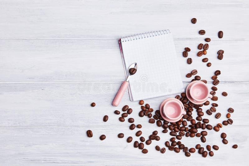 在桌上的两个小桃红色杯子与一匙子、笔记薄和疏散咖啡豆在白色木背景 免版税图库摄影