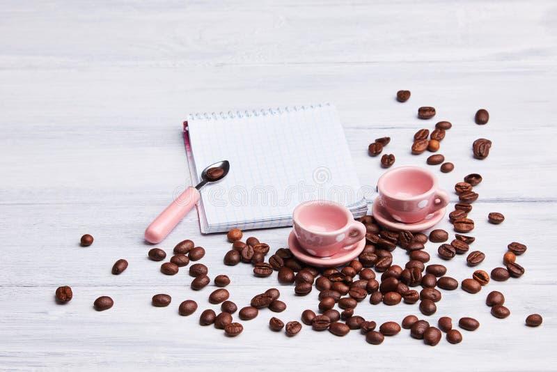 在桌上的两个小桃红色杯子与一匙子、笔记薄和疏散咖啡豆在白色木背景 免版税库存图片