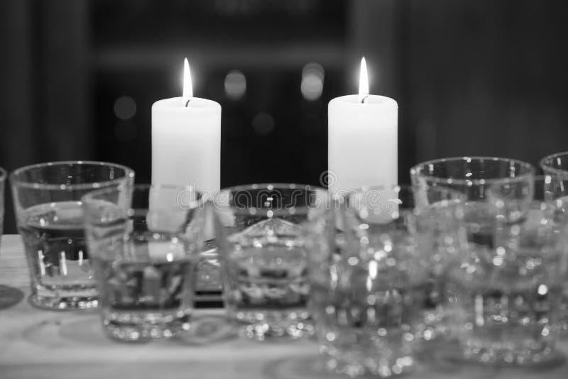 在桌上的两个灼烧的蜡烛与玻璃 黑白p 免版税库存图片
