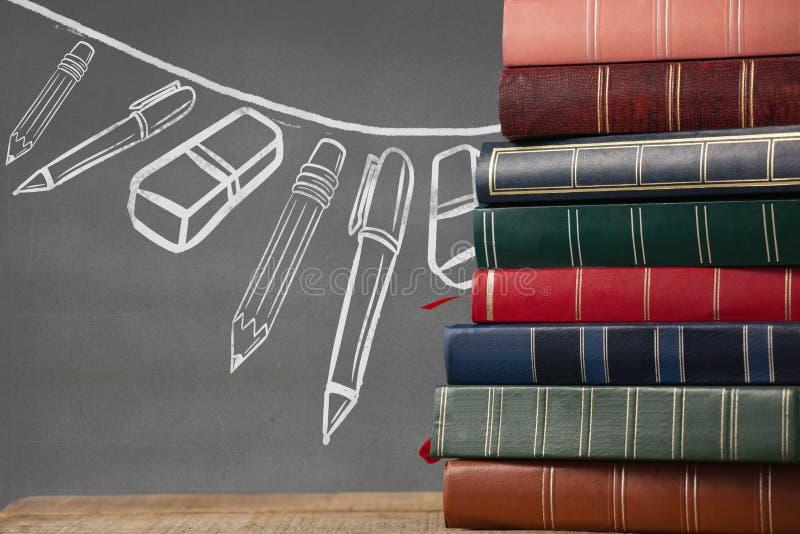 在桌上的书反对有教育和学校图表的灰色黑板 库存例证