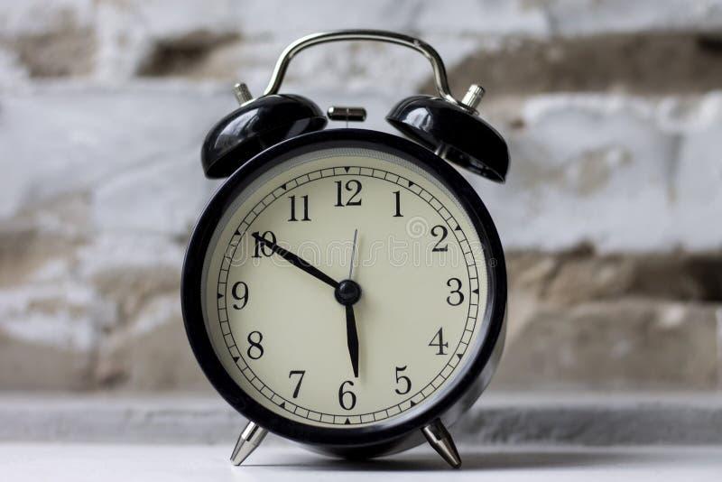 在桌上的减速火箭的闹钟在砖墙背景 免版税库存照片