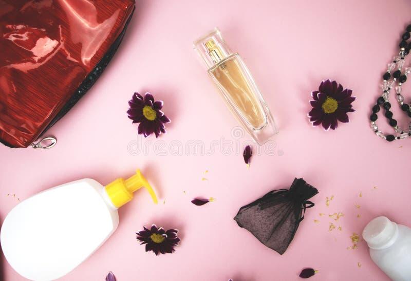在桌上的化妆用品在妇女 化妆袋子、化妆用品和卫生学方面的产品 文本的桃红色背景 免版税图库摄影