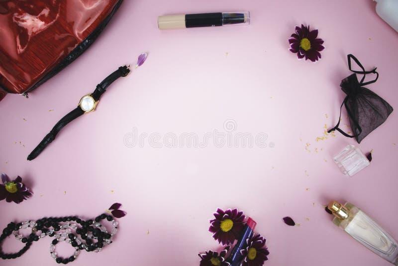 在桌上的化妆用品在妇女 化妆袋子、化妆用品和卫生学方面的产品 文本的桃红色背景 免版税库存照片
