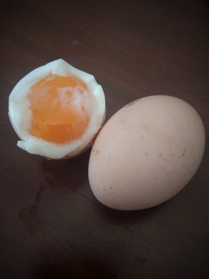 在桌上的半熟的鸡鸡蛋 免版税库存照片