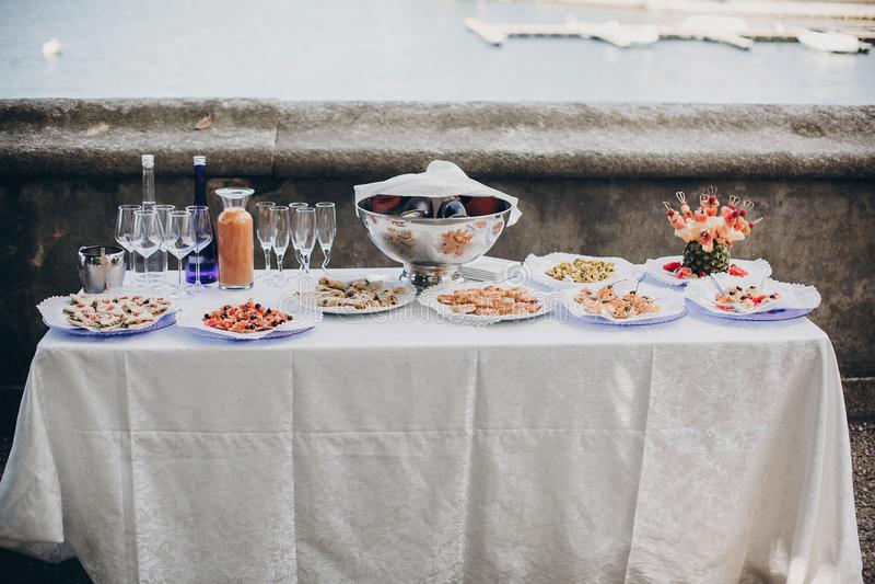 在桌上的可口意大利开胃菜在户外结婚宴会 鱼子酱、海鲜、点心、香槟和酒杯在桌上 免版税库存图片